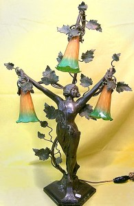 """Lovely antique Art Nouveau bronzed table lamp featuring an attractive standing lady, having intricate foliage and branches holding three green and gold ruffled-edge shades . Signed? 30""""H. Circa 1910. Working."""